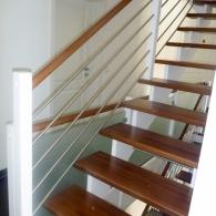 Aufgesattelte Treppe mit mitlaufenden Edelstahlstäben