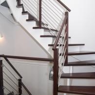 Aufgesattelte Treppe mit weißen Wangen und mitlaufendem Geländer