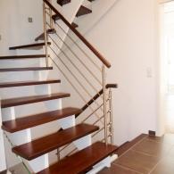 Aufgesattelte Treppe mit gebeizten Holzteilen und Edelstahlgeländer